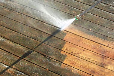 Dirty deck being powerwashed with medium pressure spray to remove grime but not damage deck.